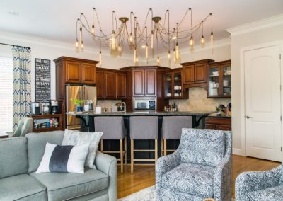 Living room chairs and adjoining kitchen area with custom cabinets